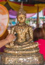 Thai tradition cover statue of Buddha with gold leaf and Hands w Royalty Free Stock Photo