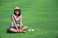 Thai woman sitting on artificial turf at garden in Kanchanaburi Thailand. Royalty Free Stock Photo