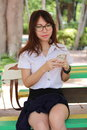 Thai woman student university beautiful girl using her smart phone portrait of Royalty Free Stock Image