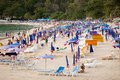 Thailand, beach: tourists, sunbeds and umbrellas Royalty Free Stock Photos