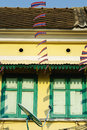 Thailand flag with wooden window on yellow house detail Stock Photos