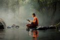 Picture : Thailand Little monk sitting on the creek or river in forest at park floating misty