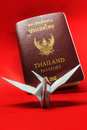 Thailand passport and paper bird on red background Royalty Free Stock Photos