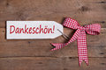 Thank you card with a red checkered ribbon on old wooden board an Stock Photo