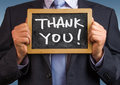 Thank you handwritten on blackboard by businessman Royalty Free Stock Image