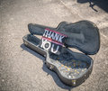 Thank you from street musician a guitar case open and filled with coins with a note the thanking for their contribution Stock Photos
