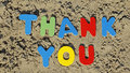 Thank you written with wooden colored letters on the beach Stock Images