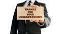 Thanks for your understanding businessman holding a sign in his hand reading in appreciation of customers standing by the business Royalty Free Stock Images