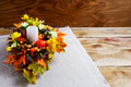 Thanksgiving  centerpiece with artificial fall leaves Royalty Free Stock Photo