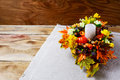 Thanksgiving  centerpiece with candle and artificial fall leaves Royalty Free Stock Photo