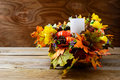 Thanksgiving decoration with white candle and silk fall leaves Royalty Free Stock Photo