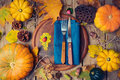 Thanksgiving dinner background with round board. Autumn pumpkin and fall leaves on wooden table. Royalty Free Stock Photo