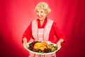 Thanksgiving dinner with grandma sweet grandmother holding a beautifully cooked turkey Royalty Free Stock Photos
