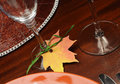 Thanksgiving dinner table close up on fall leaf glass place holder beautiful autumn theme setting with happy tag attached to Stock Photo