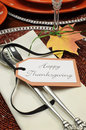 Thanksgiving dinner table place setting with close up on message beautiful autumn fall theme happy tag attached to silverware Royalty Free Stock Images