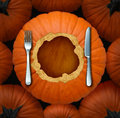 Thanksgiving food seasonal celebration concept as an autumn cuisine symbol with an orange pumpkin cut as a circular dinner plate Royalty Free Stock Images