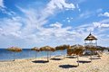 Thatch umbrellas and observation point on the beach made of wood reed black sea romania Royalty Free Stock Photo