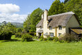 Thatched roof cottage in a typical English village. Royalty Free Stock Photo