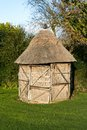 Thatched shed in garden with reed panels for sides and door Stock Photo