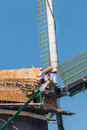 Thatcher restoring an old Dutch windmill with new reed Royalty Free Stock Photo