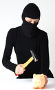 Theft breaking a masked a piggy bank with hammer isolated on white a background Royalty Free Stock Images