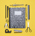 Theme book with school supplies a closed surrounded by including compass stapler tape dispenser pencil paper clips scissors back Stock Photo