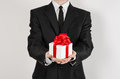 Theme holidays and gifts: a man in a black suit holds an exclusive gift in a white box wrapped with red ribbon and bow isolated on Royalty Free Stock Photo