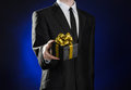 Theme holidays and gifts: a man in a black suit holds exclusive gift wrapped in a black box with gold ribbon and bow on a dark blu Royalty Free Stock Photo