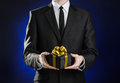 Theme holidays and gifts a man in a black suit holds exclusive gift wrapped in a black box with gold ribbon and bow on a dark blu Royalty Free Stock Images