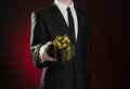 Theme holidays and gifts a man in a black suit holds exclusive gift wrapped in a black box with gold ribbon and bow on a dark red Royalty Free Stock Images