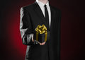 Theme holidays and gifts: a man in a black suit holds exclusive gift wrapped in a black box with gold ribbon and bow on a dark red Royalty Free Stock Photo