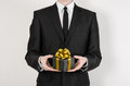 Theme holidays and gifts: a man in a black suit holds exclusive gift wrapped in a black box with gold ribbon and bow isolated on a Royalty Free Stock Photo