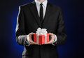 Theme holidays and gifts: a man in a black suit holds exclusive gift wrapped in red box with white ribbon and bow on a dark blue b Royalty Free Stock Photo