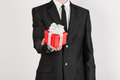 Theme holidays and gifts a man in a black suit holds exclusive gift wrapped in red box with white ribbon and bow isolated on a wh Stock Photos
