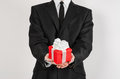 Theme holidays and gifts a man in a black suit holds exclusive gift wrapped in red box with white ribbon and bow isolated on a wh Stock Photo