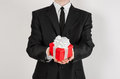 Theme holidays and gifts: a man in a black suit holds exclusive gift wrapped in red box with white ribbon and bow isolated on a wh Royalty Free Stock Photo