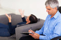 Therapist consulting patient middle aged male female in office Stock Photos