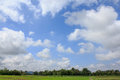 And there are beautiful white clouds bright blue sky mountains green fields below Stock Photo