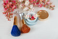 There White and Pink  Branches of Chestnut Tree,Two Make Up Brown and  Blue Brushes,Bottle Cream are on White Table Royalty Free Stock Photo