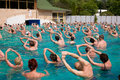 Thermal gym harkany hungary april group of people doing exercises in a pool following a woman trainer s instructions Stock Images