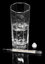 Thermometer pills and glass of water isolated on black background Royalty Free Stock Photos