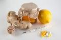 Thermometer, pills and vitamins VS jar of honey , ginger, lemon Royalty Free Stock Photo