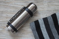 Thermos flask and scarf on a woden background. Top view Royalty Free Stock Photo