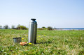 Thermos on grass field with bread a at the coast in springtime Stock Photo