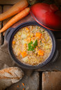 Thick vegetable soup or stew overhead view of a pot of tasty wholesome with raw carrots and fresh crusty bread alongside Royalty Free Stock Photo