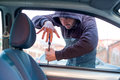 Thief breaking the car window to steal one car Royalty Free Stock Photo
