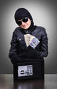 Thief holding a stolen dollars isolated on black Stock Photo