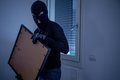 Thief inside home stealing a painting from wall