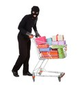 Thief pushing a trolley of gifts in black costume and balaclava shopping full and presents from celebration isolated on white Stock Image