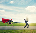 Thief running away from superwoman glad stole the bag with money and on the road at outdoor Royalty Free Stock Image